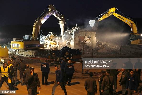 Diggers under the supervision of Israeli forces destroy a house in the Jewish settlement of Ofra in the occupied West Bank on February 28 2017...