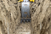 Low level view of a backhoe bucket as it digs a trench to bury an electrical power line.