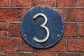 3 Digit on Dark Metal Background on red brick wall. Number three