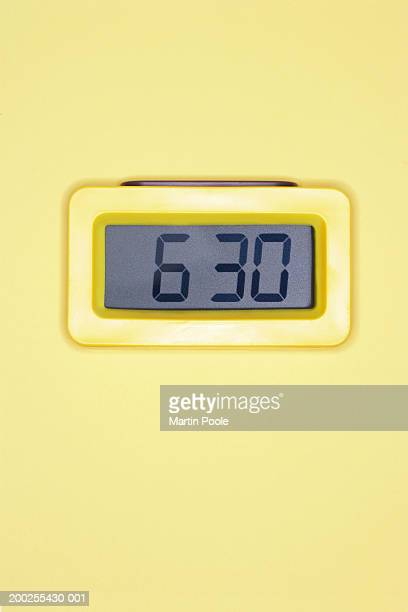 Digital alarm clock against yellow background