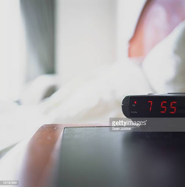 Digital alarm clock by bed in hotel room (focus on clock)