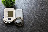 Digital measuring blood pressure, heart rate, hypertension or high blood pressure on dark grey slate background