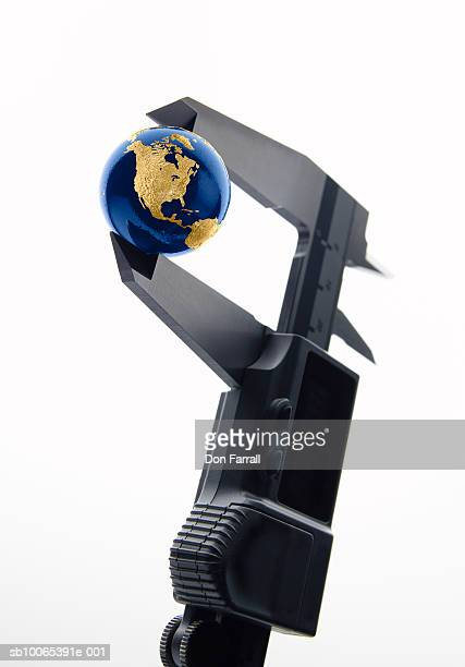 Digital caliper holding globe on white background, close-up
