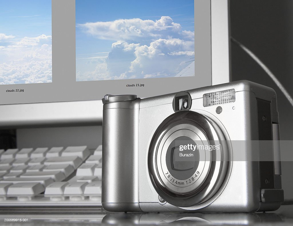Digital camera downloading to desktop computer : Stock Photo