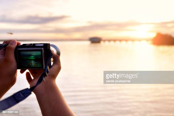 Digital camera  in boy hand  He shoots photo and nature background .