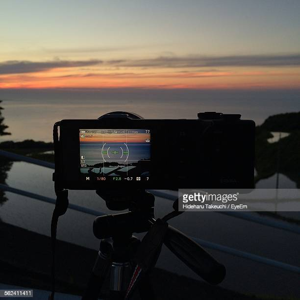 Digital Camera On Tripod Against River During Sunset