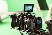 A digital cinema camera on a green screen film set.