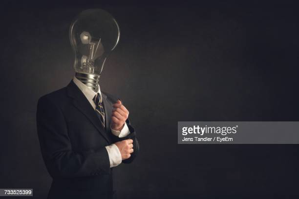 Digital Composite Image Of Businessman With Bulb Head Against Black Background