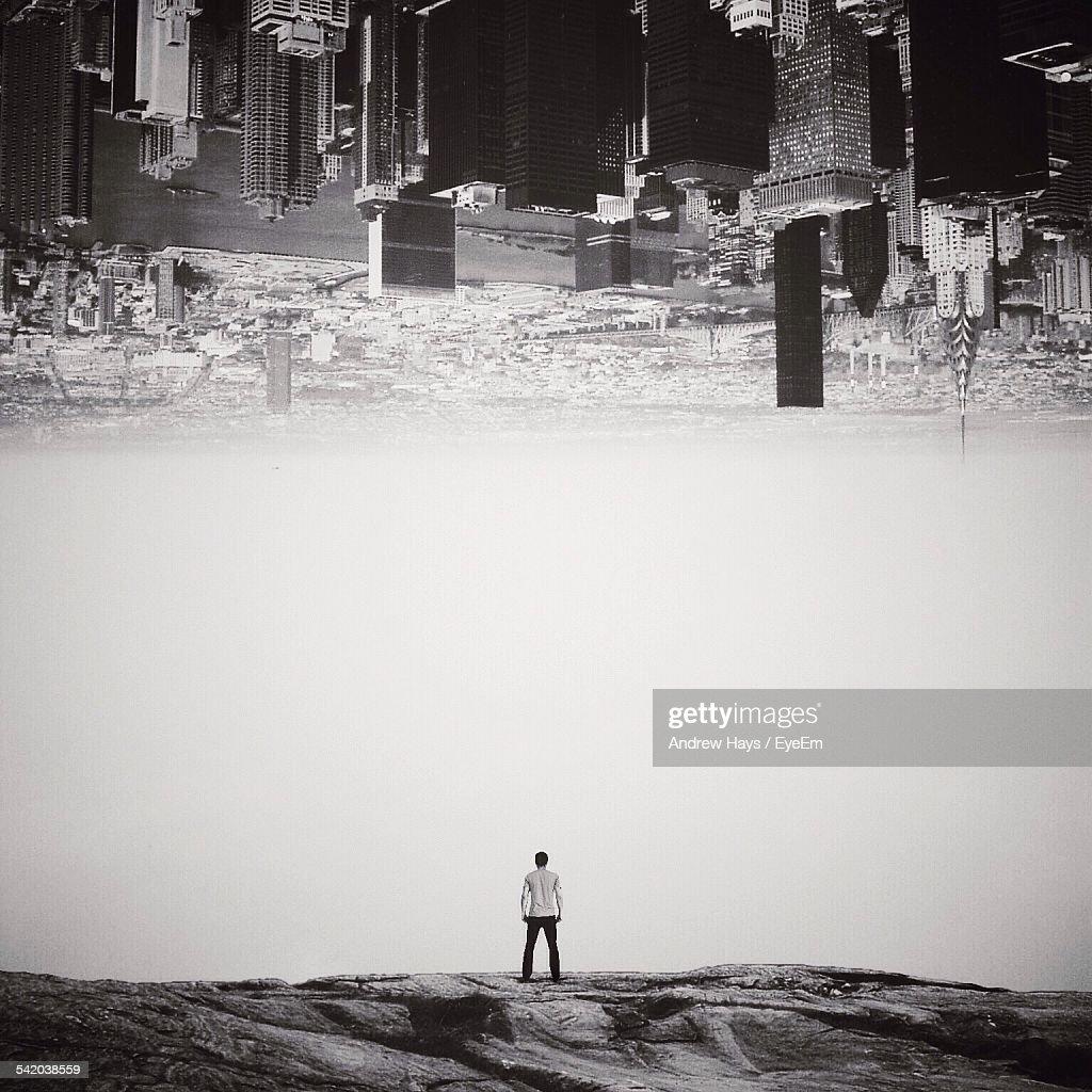 Digital Composite Image Of Cityscape Above Man Standing On Rocks