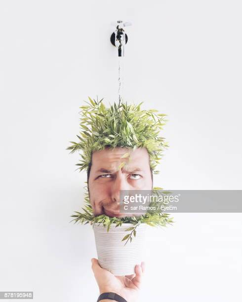 Digital Composite Image Of Man In Potted Plant Against White Background