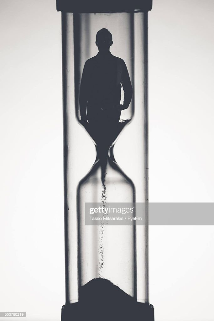 Digital Composite Image Of Man Particles Falling In Hourglass Representing Aging Process Against White Background