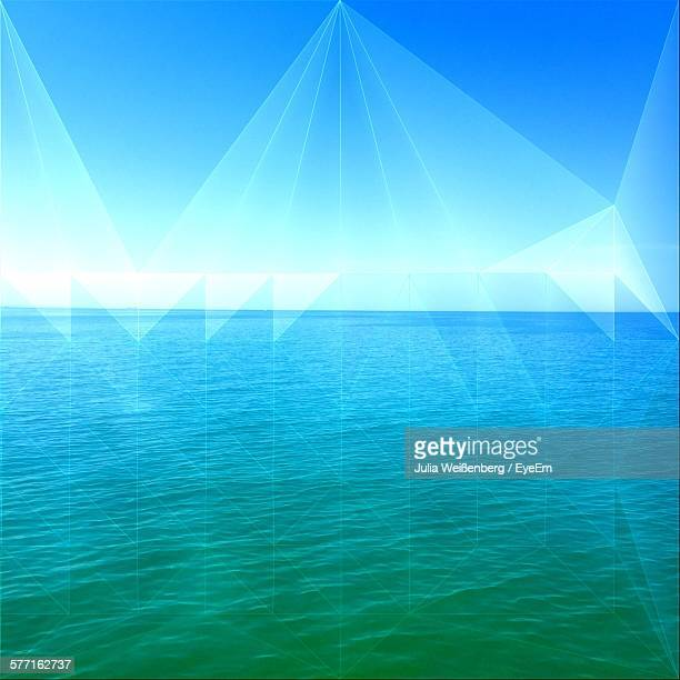 Digital Composite Of Laser Light And Sea Against Blue Sky