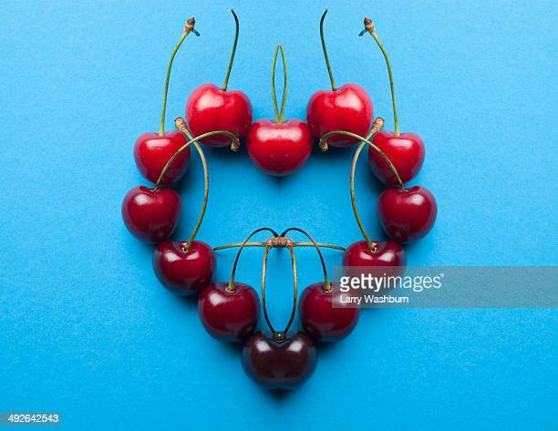 A digital composite of mirrored images of an arrangement of cherries in a heart shape