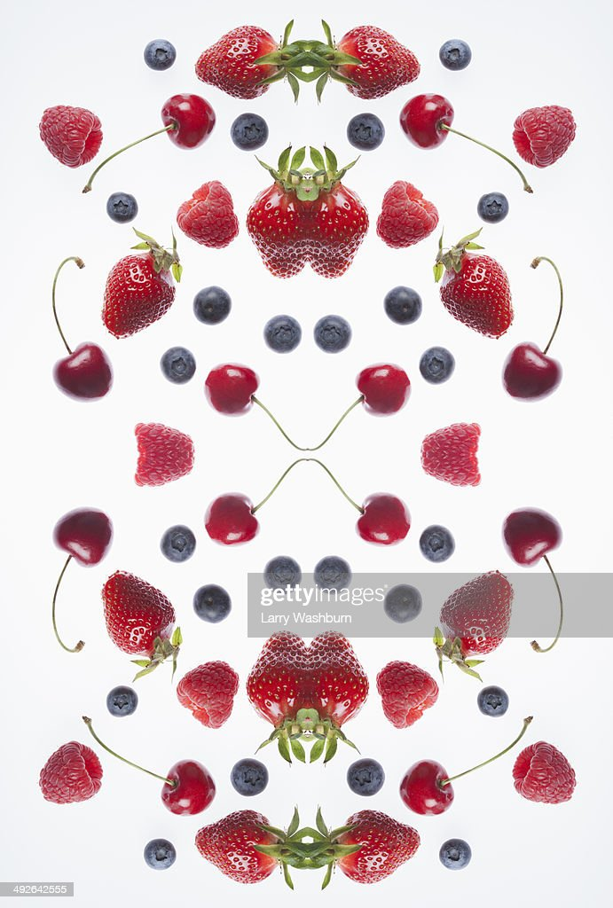 A digital composite of mirrored images of an arrangement of various berries and cherries : Stock Photo