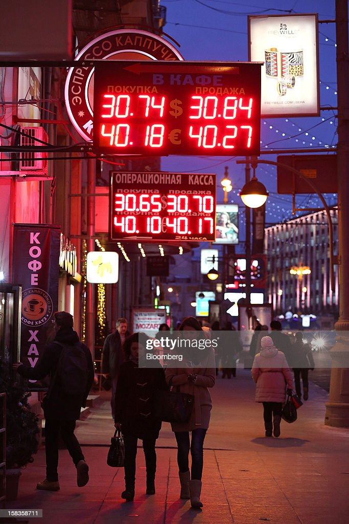 Digital currency exchange indicators hang illuminated above pedestrians on Tverskaya street in Moscow, Russia, on Thursday, Dec. 13, 2012. OAO MegaFon and its main shareholder billionaire Alisher Usmanov bought 50 percent of Euroset Holding NV in a deal that gives Russia's biggest handset retailer an enterprise value of $2.3 billion. Photographer: Andrey Rudakov/Bloomberg via Getty Images