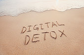 digital detox concept, words written on the sand of beach