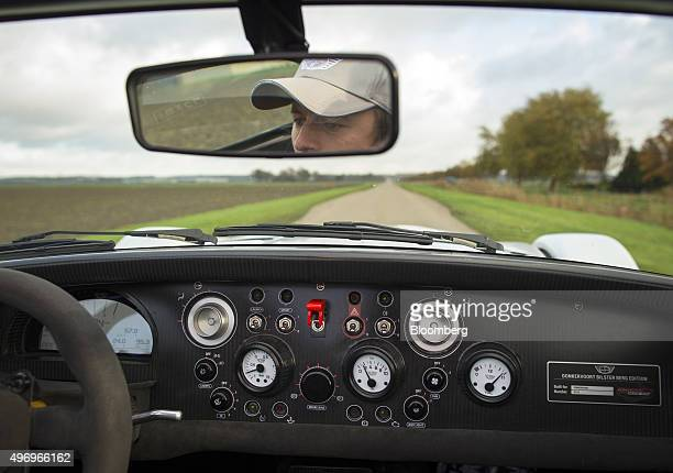 A digital display sits behind the steering wheel on the carbon fibre dashboard of a Donkervoort D8 GTO Bilster Berg Edition automobile as it speeds...