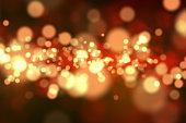 Golden and orange sparkles floating on a dark background