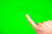 Young man types and slides on a computer screen. Digital screen with chroma key screen - green screen. Male hand.