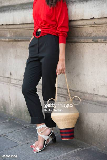 Digital Influencer Evangelie Smyrniotaki wears a Celine top and shoes Rosie Assoulin bag and Dolce and Gabbana trousers day 1 of Paris Haute Couture...