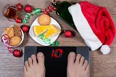 Digital scales with male feet on them and sign 'no!' surrounded by Christmas decorations, sweets and bottle of alcohol. Shows how unhealthy lifestile during xmas holidays effects our body. Top view.