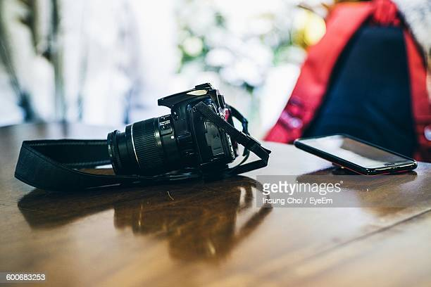 Digital Single-Lens Reflex Camera And Mobile Phone On Table