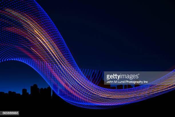 Digital stream on silhouette of city skyline at night