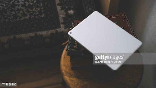 Digital Table On Stack Of Books On Wooden Table At Home