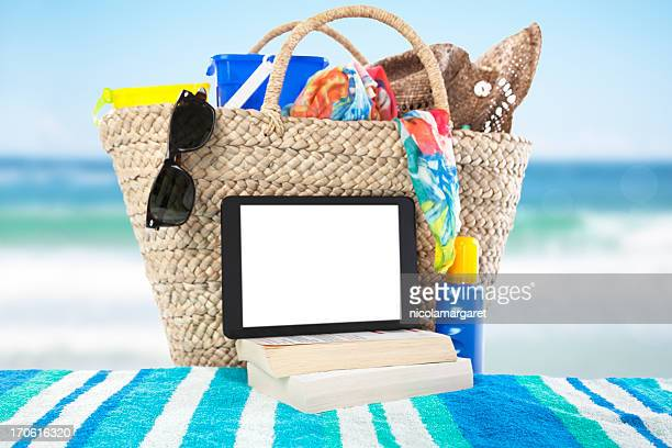 A digital tablet and books on a beach towel at the ocean
