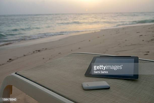 Digital tablet and smartphone on a beach