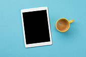 Digital tablet and coffee on blue background