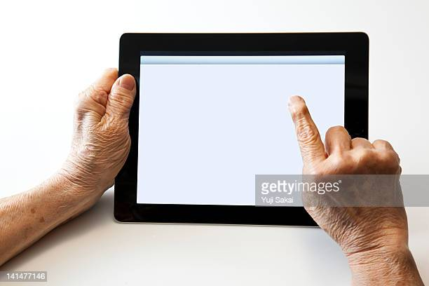 digital tablet with a hand of senior woman