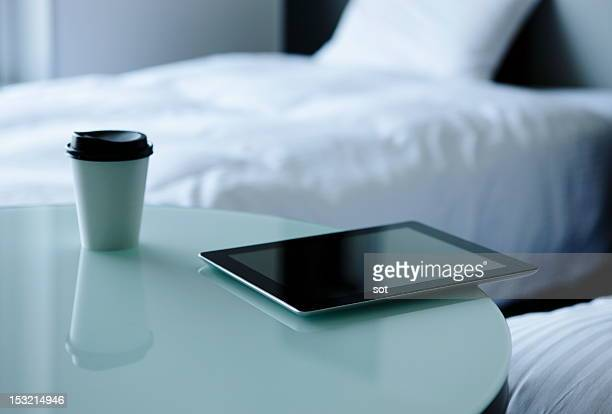 Digital tablet with coffee on table in bedroom