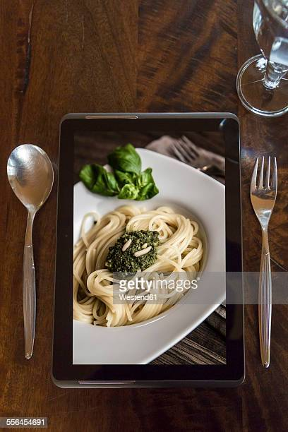 Digital tablet with photography of pasta, glass and cutlery on wood