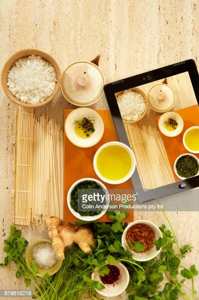 Digital tablet with picture of herbs and cooking oils next to herbs and cooking oils