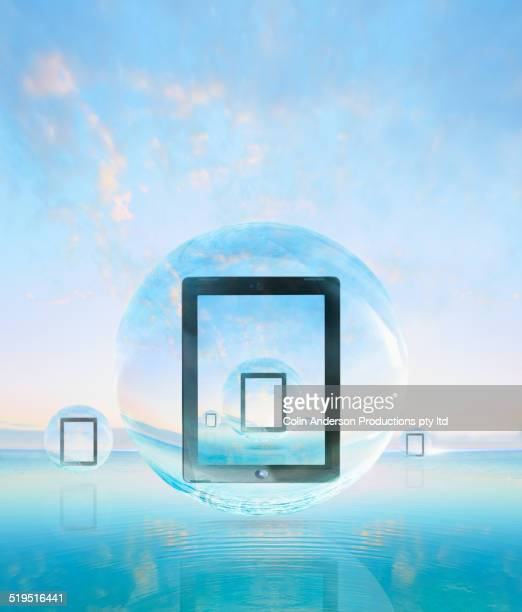 Digital tablets floating in bubbles over water