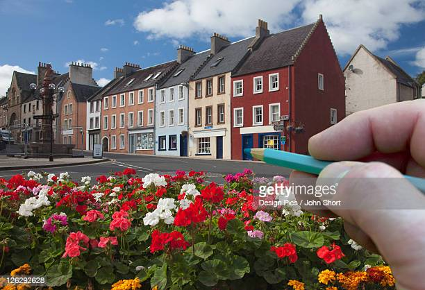 digitally enhanced image of hand holding pencil against town