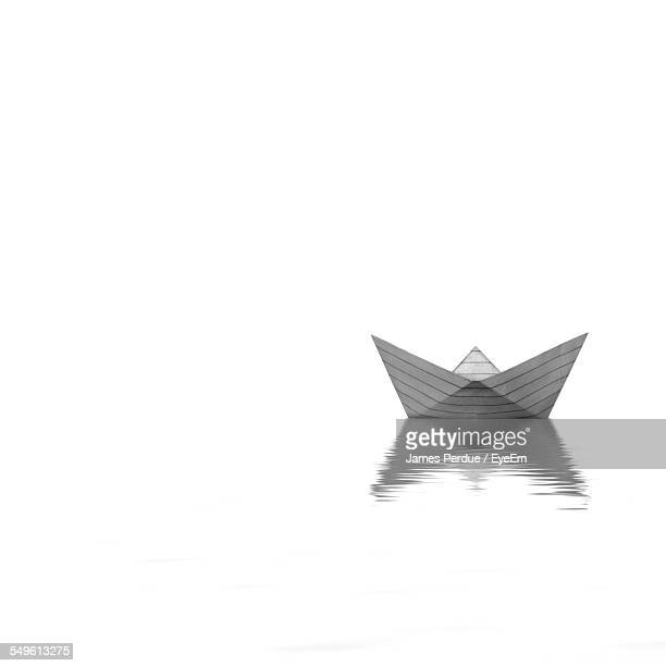Digitally Generated Image Of Paper Boat Reflecting In Water