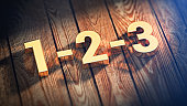 The digits '1-2-3' is lined with gold letters on wooden planks. 3D illustration pic