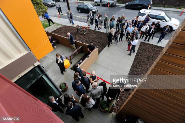 Dignitaries and crowds gather as American Family Housing chief executive Donna Gallup center prepares to take photos before cutting the ceremonial...
