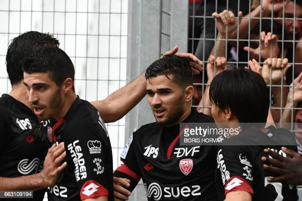 Dijon's Algerian midfielder Mehdi Abeid celebrates with his teammates after scoring during the French L1 football match Olympique of Marseille vs...