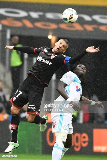 Dijon's Algerian midfielder Mehdi Abeid fights for the ball with Marseille's French forward Bafetimbi Gomis during the French L1 football match...