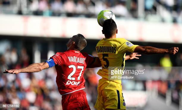 Dijon's French defender Cedric Varrault and Paris SaintGermain's Brazilian defender Marquinhos head the ball during the French L1 football match...