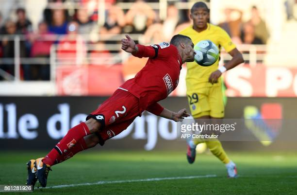 Dijon's French defender Cedric Varrault heads the ball next to Paris SaintGermain's French forward Kylian Mbappe during the French L1 football match...