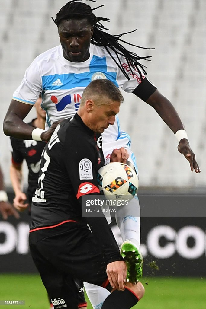 Dijon's French defender Cedric Varrault vies for the ball with Olympique de Marseille's French forward Bafetimbi Gomis (up) during the French L1 football match between Olympique of Marseille (OM) and Dijon on April 1, 2017 at the Velodrome stadium in Marseille. /
