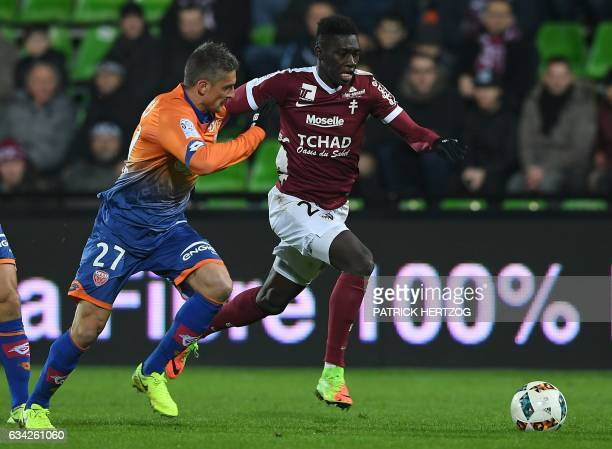 Dijon's French defender Cedric Varrault vies for the ball with Metz's Senegalese midfielder Ismaila Sarr during the French L1 football match between...