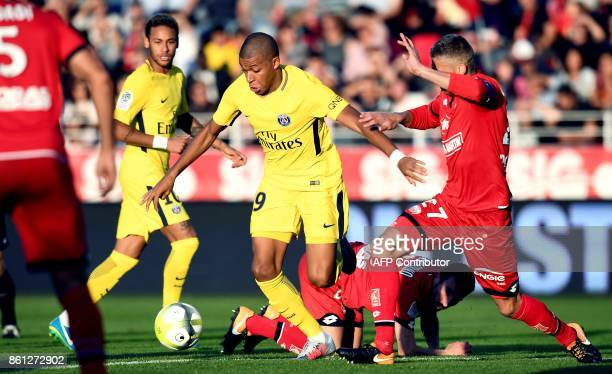 Dijon's French defender Cedric Varrault vies with Paris SaintGermain's French forward Kylian Mbappe during the French L1 football match between Dijon...