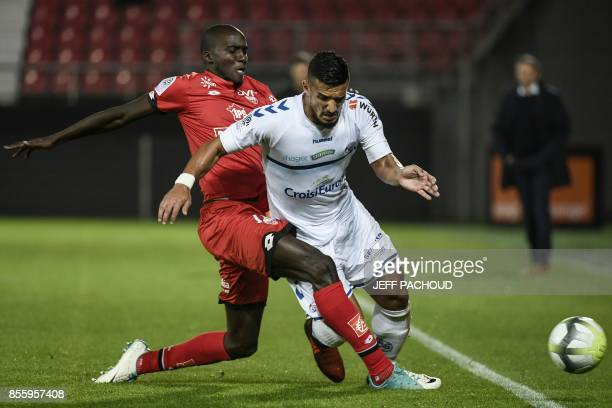 Dijon's French defender Cedric Yambere tackles Strasbourg's French forward Idriss Saadi during the French L1 football match Dijon vs Strasbourg on...