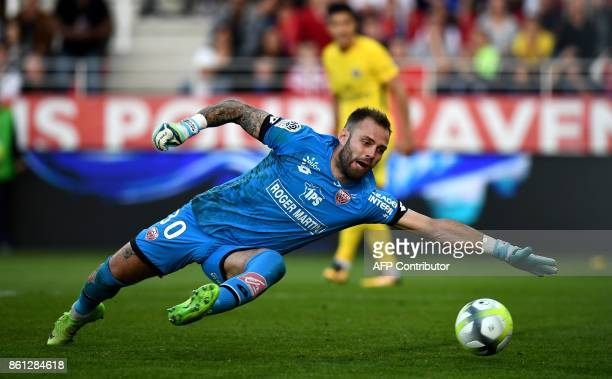 Dijon's French goalkeeper Baptiste Reynet dives as he takes a goal scored by Paris SaintGermain's Belgian defender Thomas Meunier during the French...