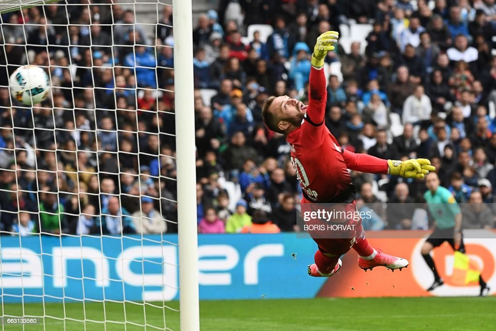 TOPSHOT - Dijon's French goalkeeper Baptiste Reynet tries to stop a score by Dimitri Payet during the French L1 football match Olympique of Marseille (OM) vs Dijon at the Velodrome stadium in Marseille on April 1, 2017. /
